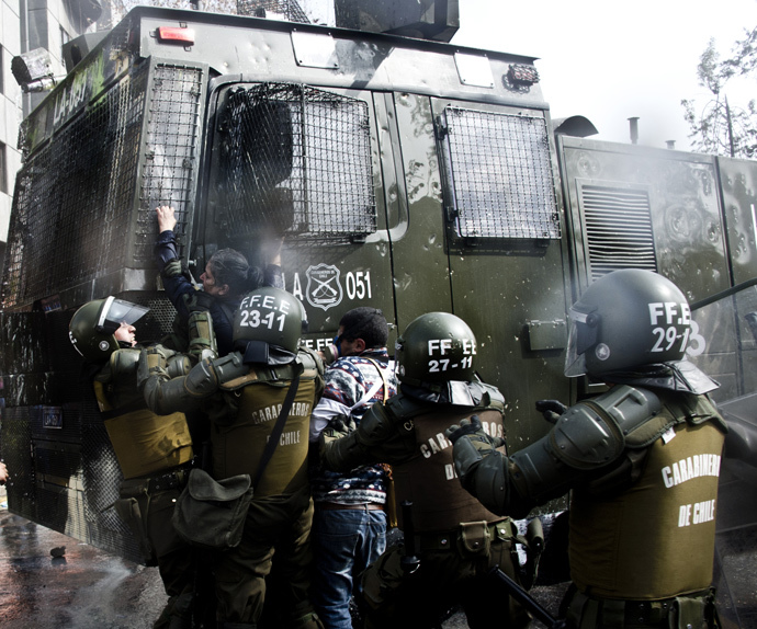 Riot police arrest a teacher during a protest to demand to Chilean President Michelle Bachelet government to improve the public education quality in in Santiago, on August 21, 2014. (AFP Photo / Martin Bernetti)