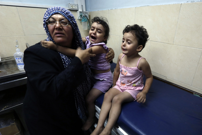 A Palestinian woman cares for wounded children at the hospital following an Israeli air strike on a house in Gaza City (AFP Photo / Mohammed Abed)