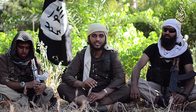 "An image grab uploaded on June 19, 2014 by Al-Hayat Media Centre shows Abu Muthanna al-Yemeni (C), believed to be Nasser Muthana, a 20-year-old man from Cardiff, Wales, speaking in an online video titled ""There is no life without Jihad"" from an undisclosed location. (AFP Photo)"