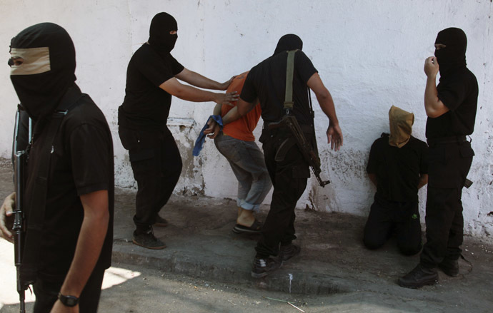 Hamas militants surround Palestinians suspected of collaborating with Israel before executing them in Gaza City August 22, 2014. (Reuters)