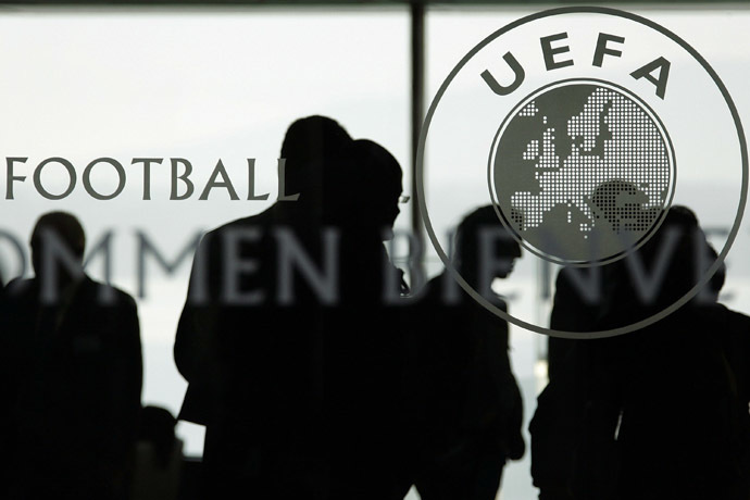 Silhouettes are seen inside the UEFA Headquarters in Nyon. (AFP Photo/Fabrice Coffrini)