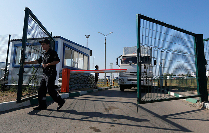 "A Russian border guard opens a gate in front of a truck from a convoy that delivered humanitarian aid for Ukraine on its return to Russia at border crossing point ""Donetsk"" in Russia's Rostov Region August 23, 2014 (Reuters / Alexander Demianchuk)"