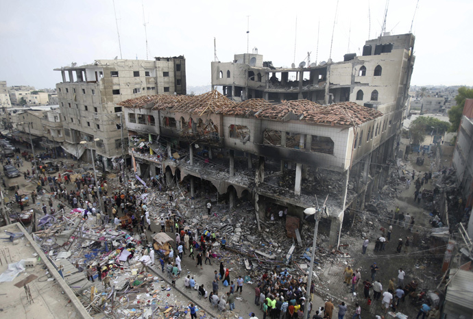 Palestinians gather around the remains of a commercial center, which witnesses said was hit by an Israeli air strike on Saturday, in Rafah in the southern Gaza Strip August 24, 2014. (Reuters / Ibraheem Abu Mustafa)