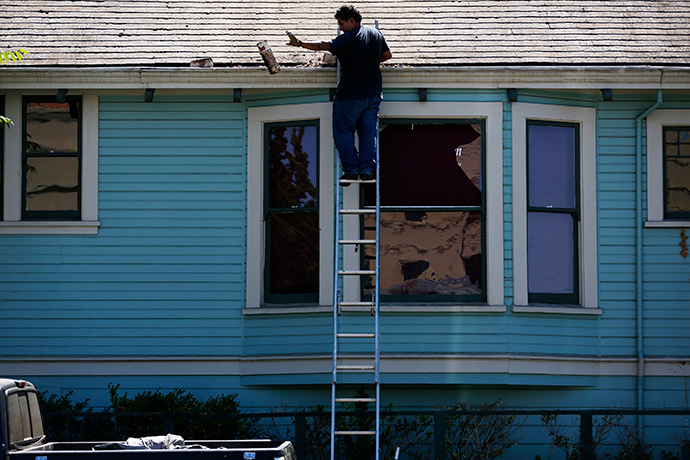 A man removes part of a fallen chimney from the roof of a house after an earthquake in Napa, California August 24, 2014 (Reuters / Stephen Lam)