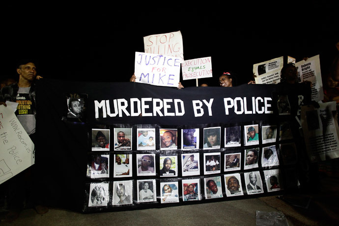 Images of people shot by police officers are displayed by demonstrators protesting the fatal shooting of Michael Brown in Ferguson, Missouri August 23, 2014.(Reuters / Joshua Lott)