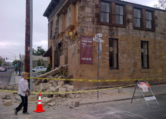 An unidentified woman walks past damage to a downtown building in Napa, California August 24, 2014.(Reuters / Jim Christie)