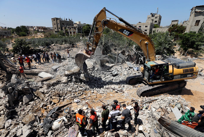 Palestinians gather as rescue workers search for victims from under the rubble of a house, which witnesses said was destroyed by an Israeli air strike, in Beit Lahiya in the northern Gaza Strip August 25, 2014.(Reuters / Mohammed Salem)