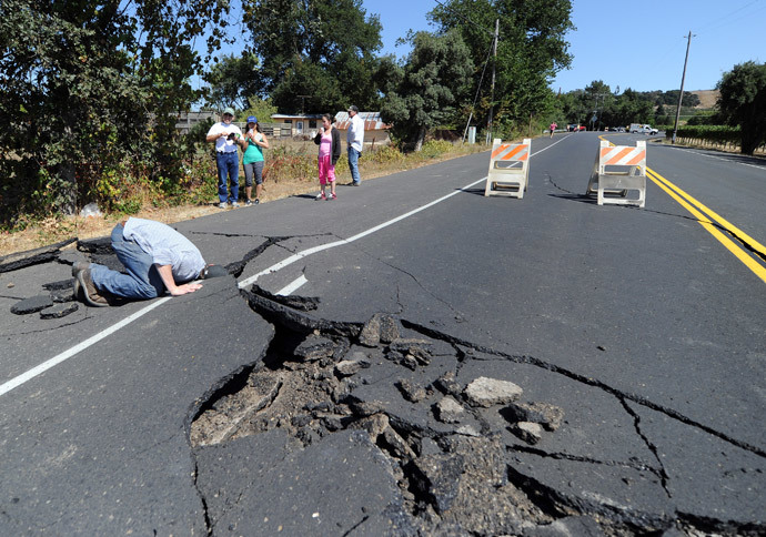 Nicholas George looks under a buckled highway just outside of Napa, California after earthquake struck the area in the early hours of August 24, 2014.(AFP Photo / Josh Edelson )