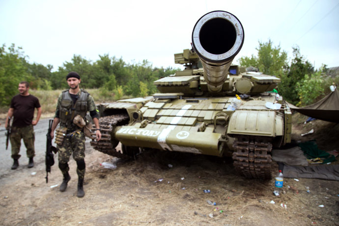 """Ukrainian troops stand beside a tank with the inscription """"victory"""", as they guard a checkpoint near the small eastern Ukrainian city of Avdiyvka, north of Donetsk.(AFP Photo / Oleksandr Ratushniak )"""