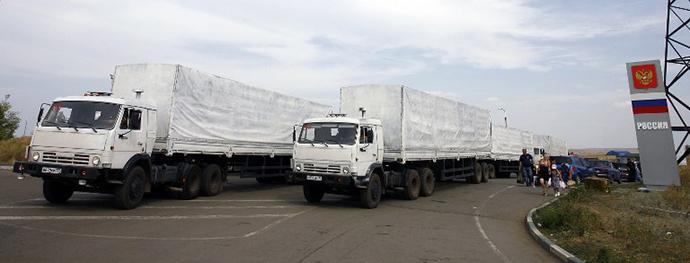 People stand by a humanitarian convoy at the Donetsk-Izvarino customs control checkpoint, some 30 km outside Kamensk-Shakhtinsky in the Rostov Region, on August 22, 2014. (AFP Photo / Sergey Venyavsky)