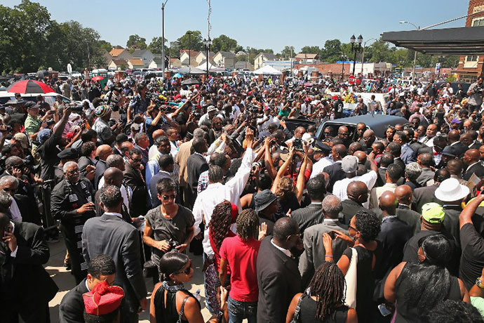 Under a crush of mourners and media the remains of Michael Brown are loaded into a hearse following his funeral services at the Friendly Temple Missionary Baptist Church on August 25, 2014 in St. Louis, Missouri. (AFP Photo / Getty Images / Scott Olson)