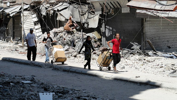 Residents of Syria's Yarmuk Palestinian refugee camp, south of Damascus, collect aid food on August 22, 2014. (AFP Photo / Rami Al-Sayed)