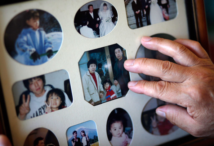 Mikio Watanabe touches a photograph of his late wife Hamako (L), himself (R) and their grandchild at his home at Yamakiya district in Kawamata town, Fukushima prefecture June 23, 2014.(Reuters / Issei Kato)