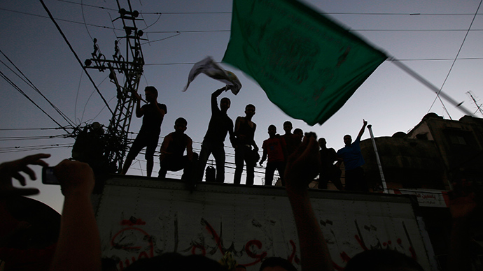 A Palestinian waves a Hamas flag (R) as others celebrate what they said was a victory over Israel, following a ceasefire in Gaza City August 26, 2014 (Reuters / Suhaib Salem)