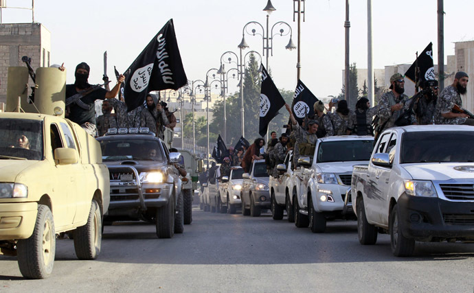 Militant Islamist fighters parade on military vehicles along the streets of northern Raqqa province June 30, 2014. (Reuters)