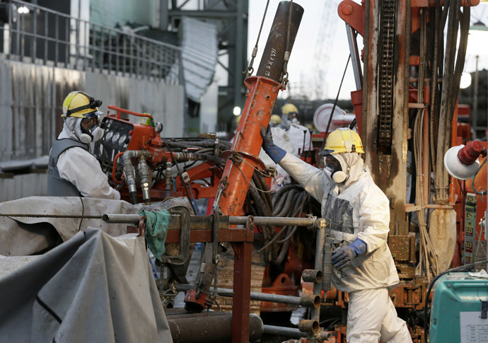 Workers prepare frozen pipes during operations to construct an underground ice wall at Tokyo Electric Power Co.'s (Tepco) tsunami-crippled Fukushima Daiichi nuclear power plant in Fukushima Prefecture July 9, 2014. (Reuters/Kimimasa Mayama)
