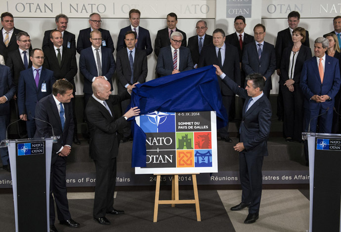 British Foreign Secretary of State for Foreign and Commonwealth Affairs William Hague (L) and NATO Secretary General Anders Fogh Rasmussen (R) unveil the logo for the upcoming NATO summit in Wales during a family photo of NATO Foreign Affairs ministers at the NATO headquarters in Brussels on June 25, 2014. (AFP Photo)