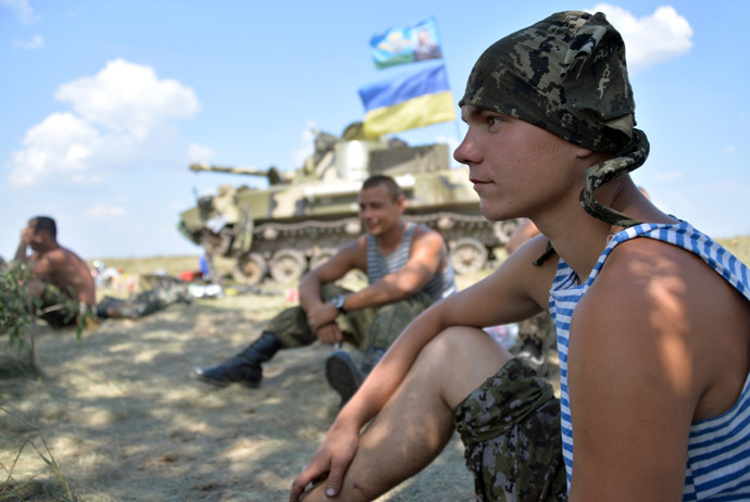 Ukrainian servicemen rest in the shade next to an armoured vehicle topped with a Ukrainian flag as they take up a position near the eastern city of Debaltceve, in the region of Donetsk, on July 30, 2014. (AFP Photo/Genya Savilov)