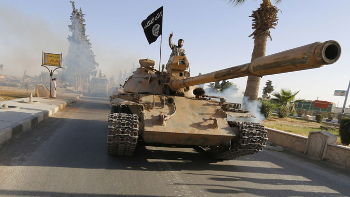 Militant Islamist fighters on a tank take part in a military parade along the streets of northern Raqqa province June 30, 2014. (Reuters)