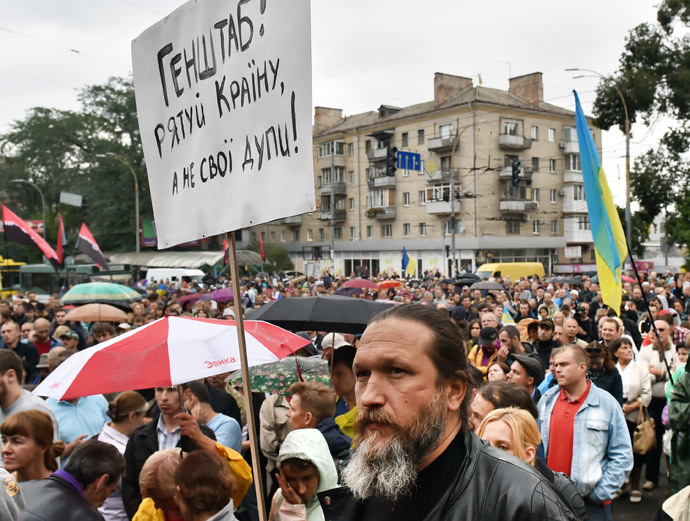 """A man holds a placard """" General Staff save Ukraine but not your asses!"""" during the rally in front of the Ukrainian Defence Ministery in Kiev on August 28, 2014.(AFP Photo / Sergei Supinsky)"""