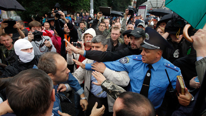 A police officer tries to prevent activists and relatives of soldiers who say that the soldiers are surrounded by self-defense forces in eastern Ukraine, from getting into the defence ministry building during a protest in Kiev August 28, 2014.(Reuters / Valentyn Ogirenko)