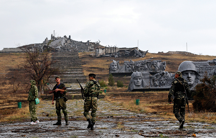 Anti-goverment fighters walk towards destroyed war memorial at Savur-Mohyla, a hill east of the city of Donetsk, August 28, 2014 (Reuters / Maxim Shemetov)