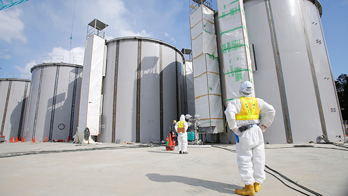 A worker wearing a protective suit and a mask looks up welding storage tanks for radioactive water, under construction in the J1 area at the Tokyo Electric Power Co's (TEPCO) tsunami-crippled Fukushima Daiichi nuclear power plant in Okuma in Fukushima prefecture (AFP Photo / Toru Hanai)