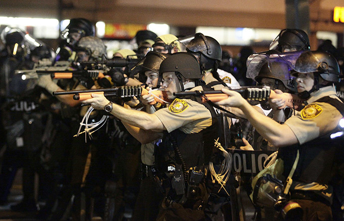 Police officers point their weapons at demonstrators protesting against the shooting death of Michael Brown in Ferguson, Missouri August 18, 2014. (Reuters / Joshua Lott)