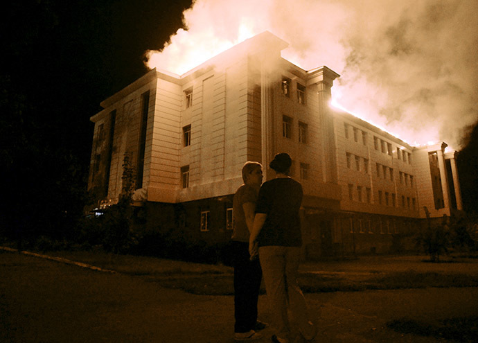 Bystanders watch a fire consuming a school in downtown Donetsk on August 27, 2014, after being hit by a shelling. (AFP Photo / Francisco Leong)