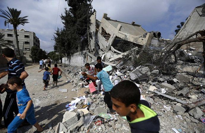 Palestinian children run near what remains of Ali ibn Abi Taleb government school after it was targeted overnight by Israeli airstrikes on August 26, 2014 in Gaza City. (AFP Photo / Mohammed Abed)