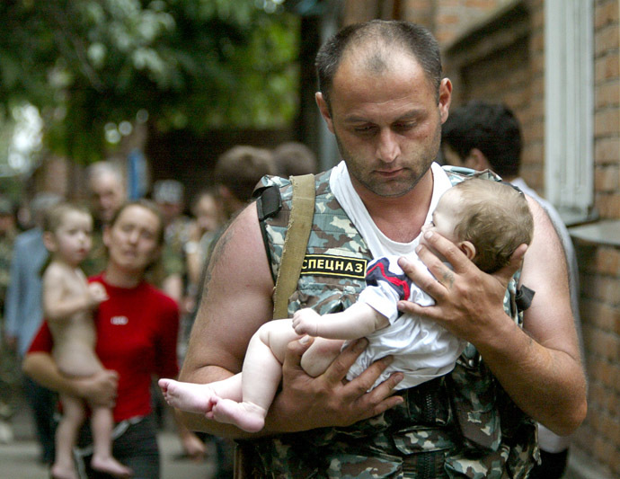 Russian police officer carries a released baby from the school seized by heavily armed masked men and women in the town of Beslan. (Reuters/Viktor Korotayev)
