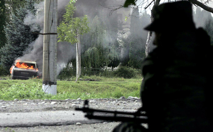 A Russian soldier waits on his position as a car burns outside the school where a group of gunmen, wearing belts laden with explosives, are holding civilian hostages in a school in the northern Ossetian town of Beslan, some 30 kms outside Vladikavkaz, 02 September 2004. (AFP Photo/Maxim Marmur)