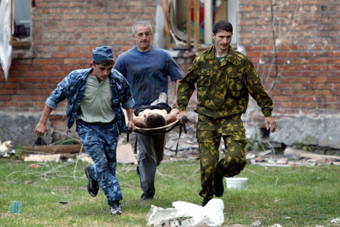Volunteers carry an injured civilian to safety after soldiers stormed a school seized by heavily armed masked men and women in the town of Beslan in the province of North Ossetia near Chechnya , September 3, 2004. (Reuters)