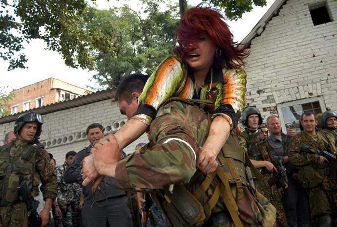 A Russian special forces soldier carries an injured woman during the rescue operation of Beslan's school, northern Ossetia, 03 September 2004. (AFP Photo/Yuri Tutov)