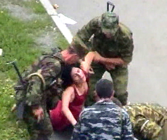 This TV-grab image shows Russian soldiers helping an injured woman during the rescure operation in Beslan, North Ossetia 03 September 2004. (AFP/NTV)