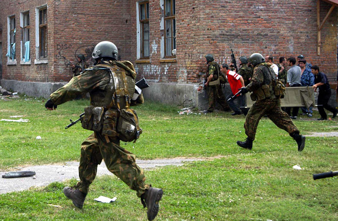 Russian special forces soldiers run during the rescue operation of Beslan's school, northern Ossetia, 03 September 2004. (AFP Photo/Yuri Tutov)