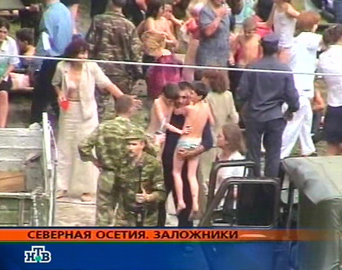 This TV-grab image taken from Russian NTV channel shows hostages in the school garden during the rescue operation in the town of Beslan, North Ossetia 03 September 2004. (AFP/NTV)