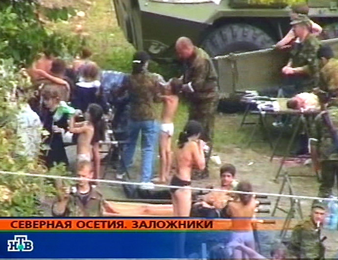 This TV-grab image taken from Russian channel NTV shows hostages in the school garden during the rescue operation 03 September 2004 in the town of Beslan, North Ossetia. (AFP/NTV)