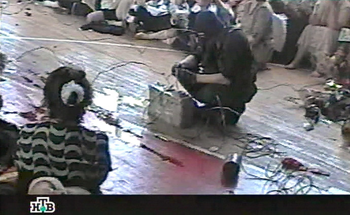 This TV grab image taken from Russian NTV channel 07 September 2004 shows a gunman connecting wires as hostages sit in the gymnasium of the Beslan school, northern Ossetia. (AFP/NTV)