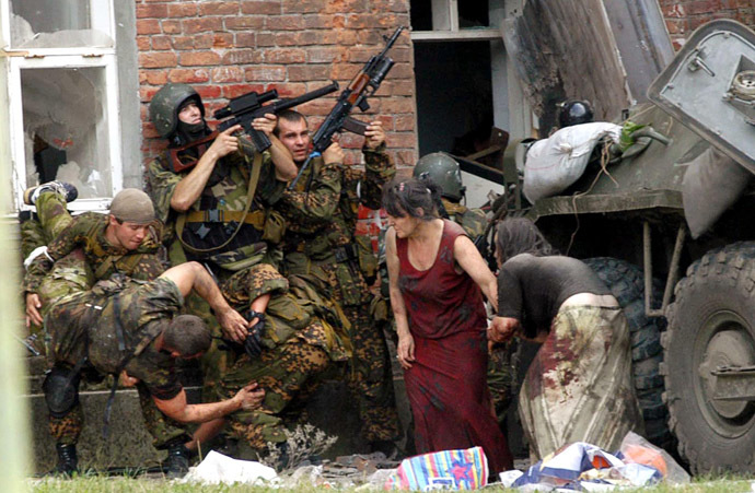 A Russian special police soldier (L) carries an injured colleague as two soldiers and two women take cover behind the APC during the rescue operation of Beslan's school, northern Ossetia, 03 September 2004. (AFP Photo/Yuri Tutov)