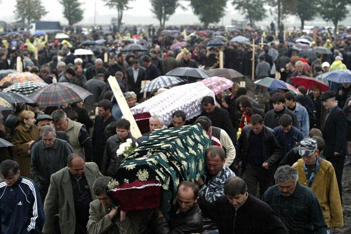Relatives of victims who died in the Beslan school hostage siege carry coffins under the heavy rain at the cemetery in Beslan, North Ossetia, 06 September 2004. (AFP Photo/Viktor Drachev)