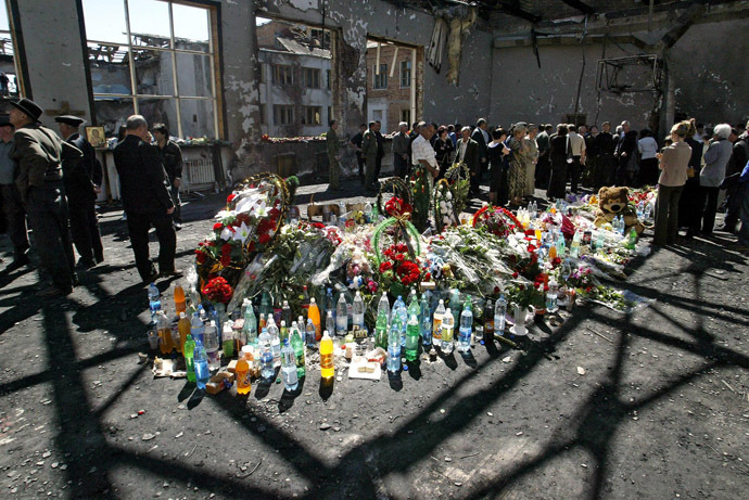 Ossetians mourn around flowers and bottles of water at the gymnasium of the destroyed school in Beslan, North Ossetia, 08 September 2004. (AFP Photo/Victor Drachev)