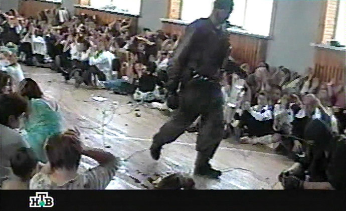 This TV grab image taken from Russian NTV channel 07 September 2004 shows a gunman walking as hostages sit in the gymnasium of the Beslan school, northern Ossetia. (AFP/NTV)