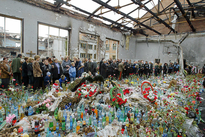 Ossetians mourn at the destroyed school's gymnasium in Beslan 12 October 2004. (AFP Photo/Maxim Marmur)