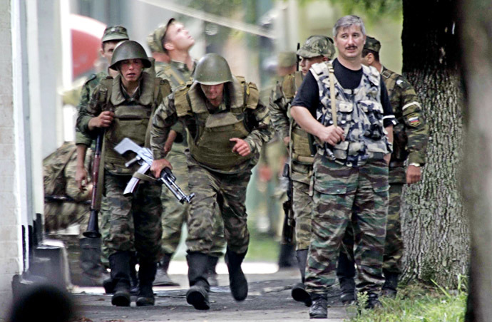 Russian soldiers take position outside the school, where a group of gunmen, wearing belts laden with explosives, are holding hostage some 350 people in the northern Ossetian town of Beslan, some 30 kms outside Vladikavkaz, 02 September 2004. (AFP/ITAR-TASS)