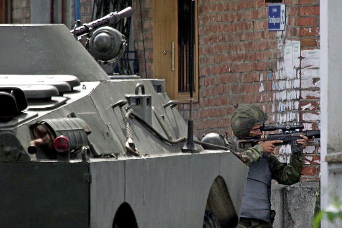 A Russian special forces soldier aims at a position outside the school, where a group of gunmen, wearing belts laden with explosives, are holding hostage some 350 people in the northern Ossetian town of Beslan, some 30 kms outside Vladikavkaz, 02 September 2004. (AFP/ITAR-TASS)