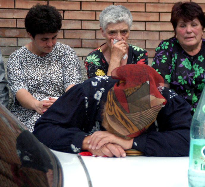 Relatives of school children being held hostage wait for further developments as they sit near the seized school in the town of Beslan, province of North Ossetia near Chechnya, September 1, 2004. (Reuters)