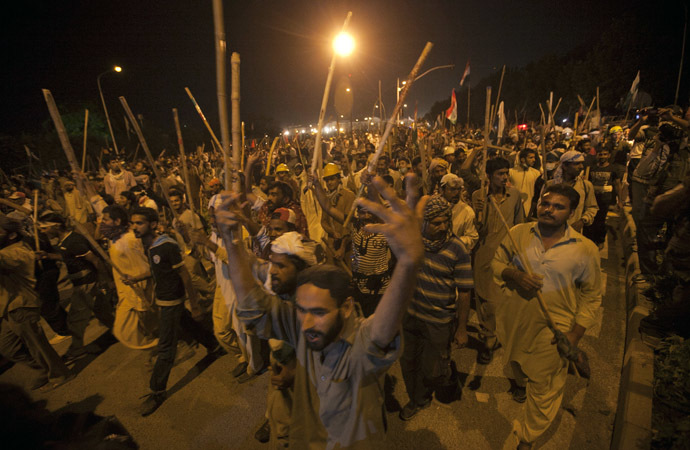 Supporters of Tahir ul-Qadri, Sufi cleric and leader of political party Pakistan Awami Tehreek (PAT), carry sticks as they move towards the Prime Minister's house during the Revolution March in Islamabad August 30, 2014. (Reuters/Akhtar Soomro)