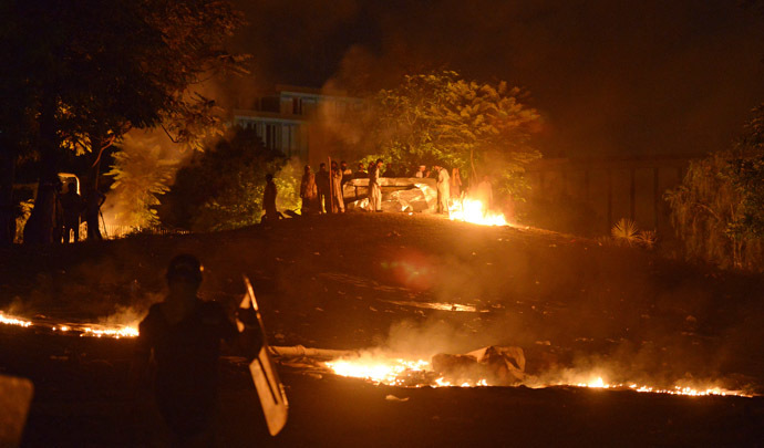 Supporters of cricketer-turned-politician Imran Khan and Canadian cleric Tahir ul Qadri take position alongside fire near the prime minister's residence following clashes with security forces in Islamabad on August 31, 2014. (AFP Photo)