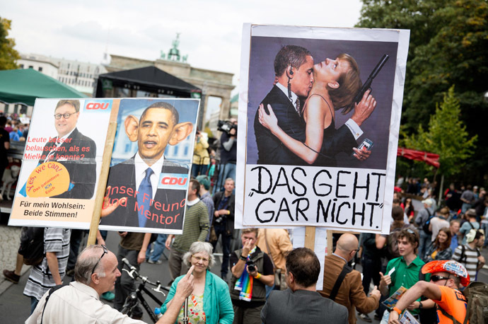 "A demonstrator holds a placard depicting German chancellor's Angela Merkel and US President Barck Obama reading ""That does not work"" (Das geht gar nicht) during a demonstration against governmental surveillance on August 30, 2014 in Berlin. (AFP/DPA)"